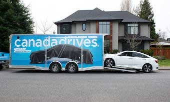 Certified pre-owned vehicle purchased online gets delivered to the home of a customer in a Canada Drives branded trailer